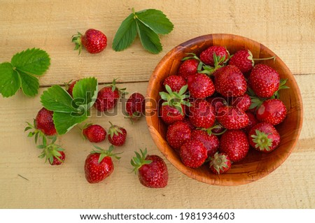 Fresh mellow strawberry in wooden bowl on wooden background Foto stock ©