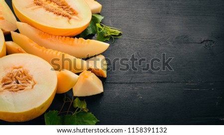 Fresh melon Sliced to pieces of melon. On a black wooden background. Free space for text. Top view.