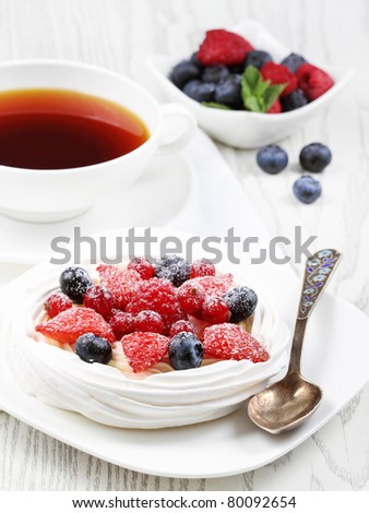 Fresh meringue with thick cream and fruits on a plate