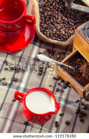 Fresh milk and ground coffee in the grinder