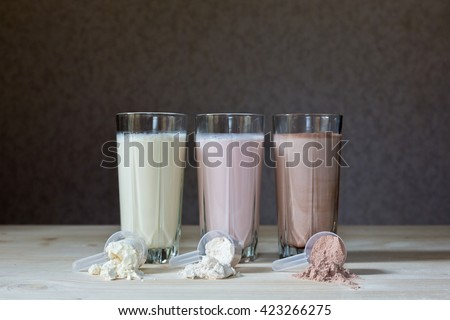 Fresh milk, chocolate, blueberry and banana drinks on table, assorted protein cocktails.