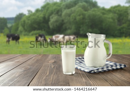 Fresh milk in glass on dark wooden tabletop and blurred landscape with cow on meadow. Healthy eating. Rustic style. Space for design.