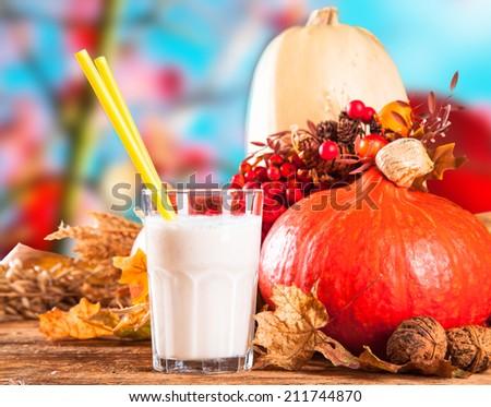 Fresh milk shake, autumn leaves with season vegetable on wooden table