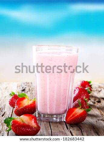 Fresh milk, strawberry drink on wodeen table, assorted protein cocktail with fresh fruits. Summer drink on the beach and blue sky.