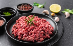 Fresh minced meat ground beef on a black plate against stone background
