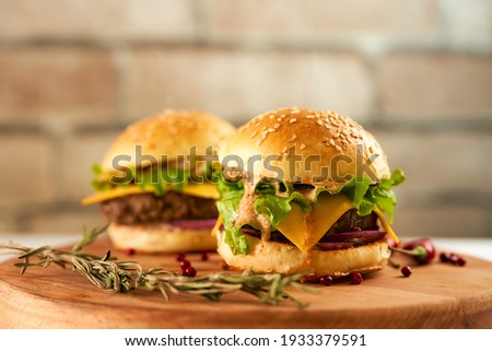 Fresh mini burgers on a deerved tray against a brick wall
