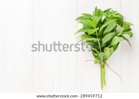 Fresh mint bunch on white wooden table. Top view with copy space