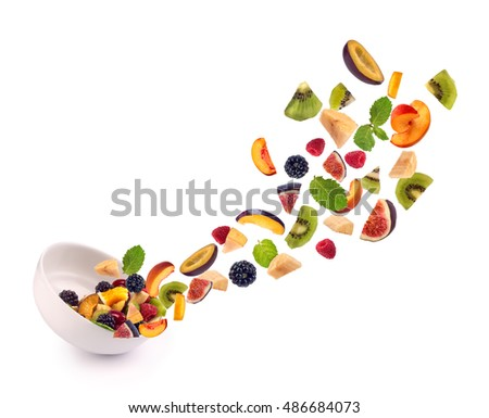Fresh mixed fruits pieces falling in white bowl of  fruit salad isolated on white