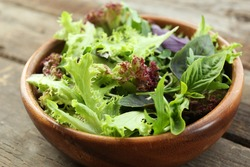 Fresh mixed green salad in bowl on wooden table close up