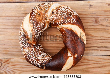 fresh mixed pretzels topped by sesame on wooden table - stock photo