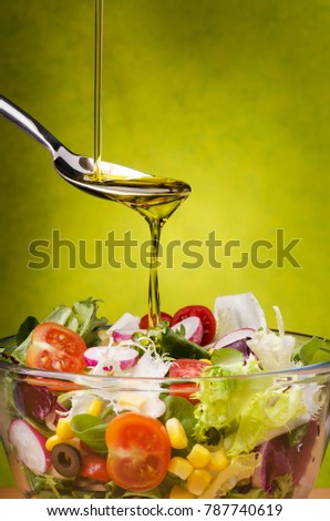 fresh mixed salad topped with a drizzle of olive oil on a green background