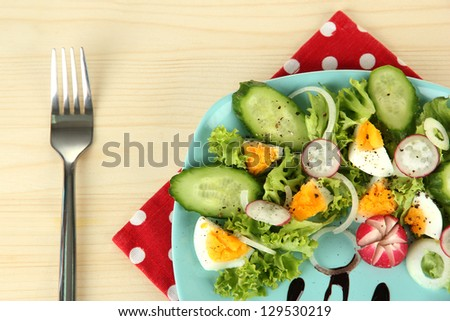 Fresh mixed salad with eggs, salad leaves and other vegetables on color plate, on wooden background - stock photo