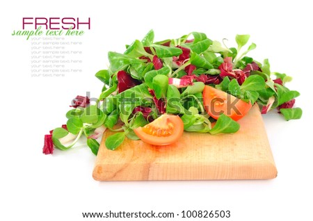 Fresh mixed salad with tomatoes on a wooden board isolated on white background