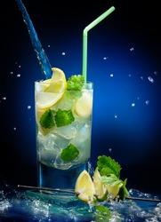Fresh mojito cocktail  on wet dark blue background