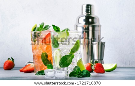 Fresh Mojito cocktail set with lime, mint, strawberry and ice in glass on gray background. Summer cold alcoholic non-alcoholic drinks, beverages and cocktails. Steel bar tools. Copy space
