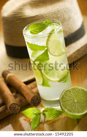 fresh mojito with cuban cigars and hat in background