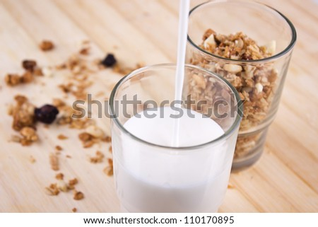 Fresh muesli and milk close up. Delicious and healthy granola or muesli, with lots of dry fruits, nuts and grains