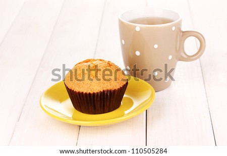 Fresh muffin with tea on wooden background