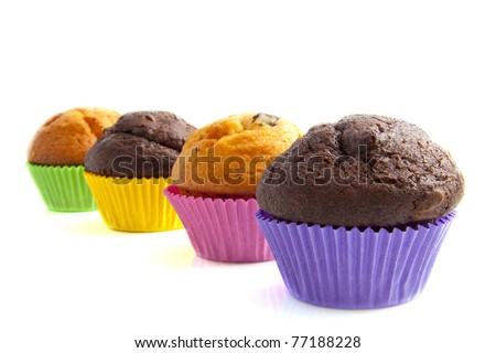Fresh muffins in colorful cups isolated over white