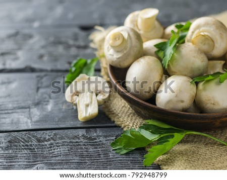 Fresh mushrooms in a clay bowl and parsley on a dark rustic wooden table. Vegetarian food is on the table.