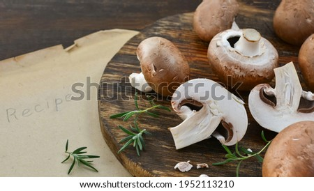 Fresh mushrooms on old wooden board with rosemary sprigs  with old sheets of paper with the inscription 'Recipes' close-up. Сток-фото ©