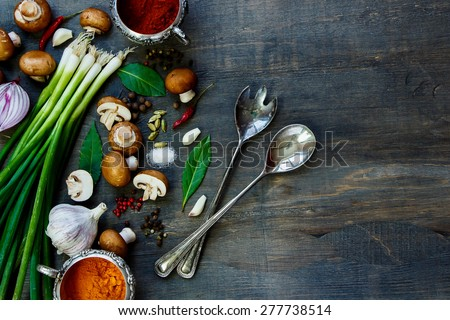 Fresh mushrooms with vegetables and spices on dark wooden table. Background with space for text. Vegetarian food, health or cooking concept.