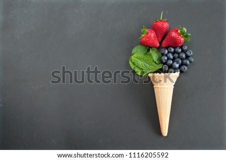 Fresh natural flavors pouring out of an icecream cone including strawberry, mint and blueberries #1116205592