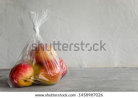 Fresh natural fruit in plastic bag on grey background. The concept of harm of food storage in artificial packages.