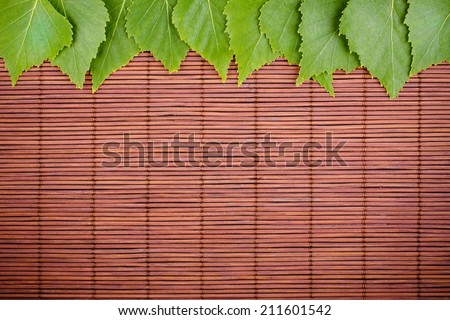 Fresh Natural Green Leaves on Dark Brown Bamboo Mat, Ecology Background