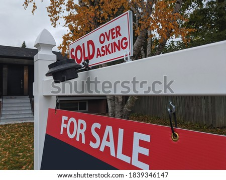 Fresh new sign sold over asking for sale in front of detached house in residential area. Real estate bubble, crash, hot housing market, overpriced property, buyer activity concept. Selective focus.