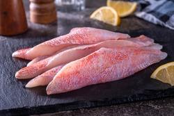 Fresh ocean perch Acadian redfish fillets on a slate board.