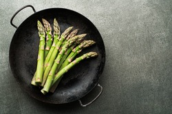 Fresh of green Asparagus. Cooking healthy meal in pan. Bunches of green asparagus, top view- Image