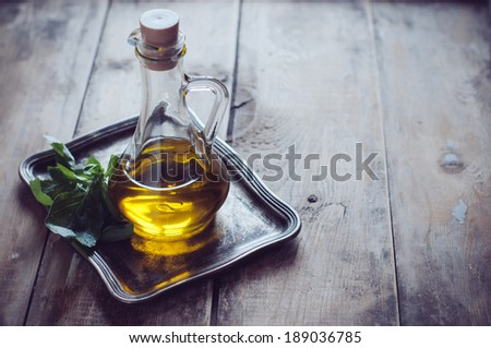 Fresh olive oil in a vintage bottle and bunch of green basil on a metal tray on a wooden board
