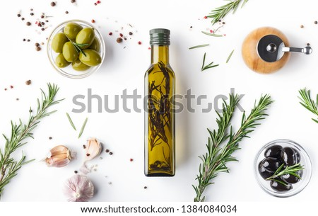 Fresh olives and oil in bottle with rosemary on white background with scattered spicies, top view. Organic olive oil concept