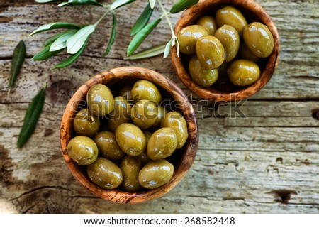 Fresh olives and olive oil  on rustic wooden background. Olives in olive wood.