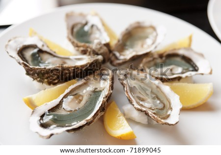 Fresh open oysters on plate with lemon, selective focus