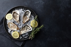 Fresh opened oysters in a plate with ice and lemon on black textured background, top view