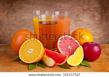 fresh orange, apple and grapefruit juice and fruits on a wooden background