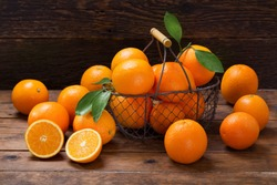fresh orange fruits with leaves in a basket on wooden table