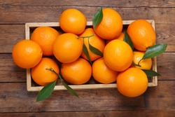 fresh orange fruits with leaves in a box on wooden table, top view