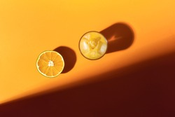 Fresh orange juice glass with ice and half of orange fruit, in sunlight. Above view of citrus fruit and summer refreshment on orange background.