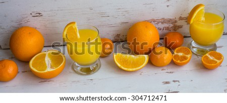 Fresh orange juice in a glass on a white wooden table. Cut slices of orange and juice.