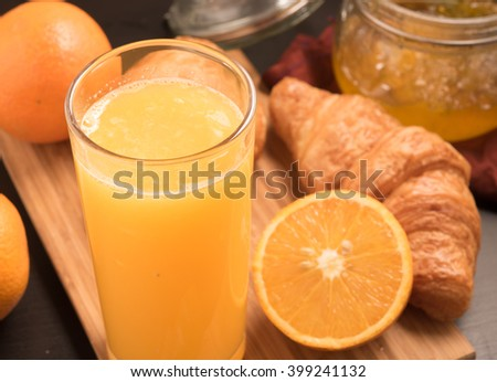 fresh orange juice in a glass with Croissant and jam #399241132