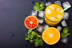 Fresh orange juice,  mint and ice on dark background, top view, copy space