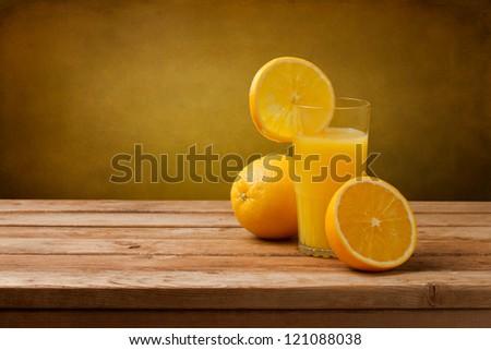Shutterstock Fresh orange juice on wooden table over grunge background