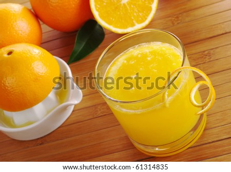 Fresh orange juice with orange slice in glass with squeezer and oranges in background on table mat (Selective Focus) - stock photo