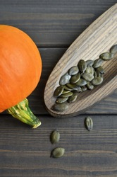 Fresh orange pumpkin with dry styrian pumpkin seeds on wooden plate over dark old wooden table background, top view.