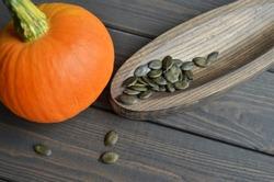Fresh orange pumpkin with organic pumpkin seeds on wooden plate over dark old wooden table background, top view.
