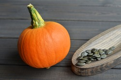 Fresh orange pumpkin with organic pumpkin seeds on wooden plate over dark wooden table background, side view.