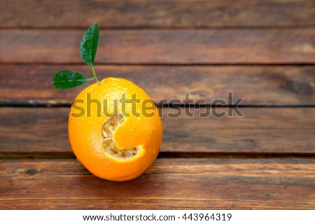 Fresh orange with letter C cut into it resembling vitamin C placed on wooden table #443964319